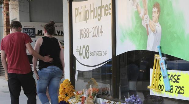 A couple leave after laying a shopfront floral tribute to cricketer Phillip Hughes in his home town of Macksville (AP)