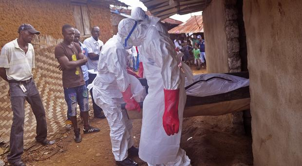 Health workers carry the body of a man suspected to have died of Ebola in the village of Gbah on the outskirts of Monrovia (AP Photo/ Abbas Dulleh)