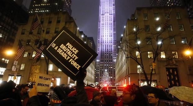 Protesters march down Fifth Avenue, New York, past the Rockefeller Centre Christmas tree (AP)