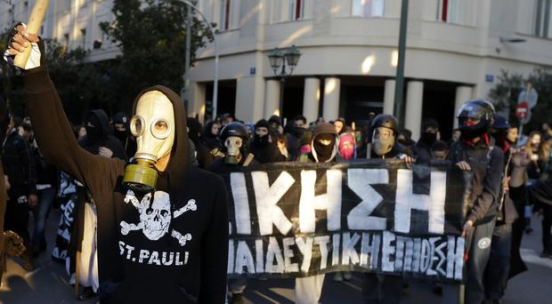 Masked youths hold a banner bearing the word
