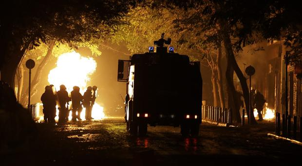 Police bring in a water cannon as petrol bombs are hurled in the Athens neighbourhood of Exarchia (AP)