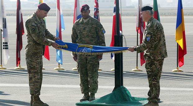 International Security Assistance Force Joint Command Lt Gen Joseph Anderson, left, folds the flag of IJC at Kabul International Airport (AP)