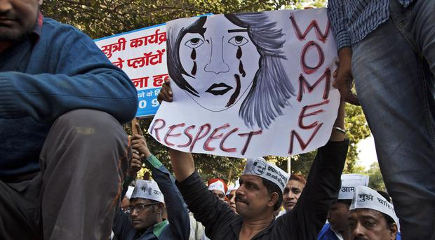 Protesters hold placards during a protest after a woman was allegedly raped by a taxi driver in New Delhi, India (AP)