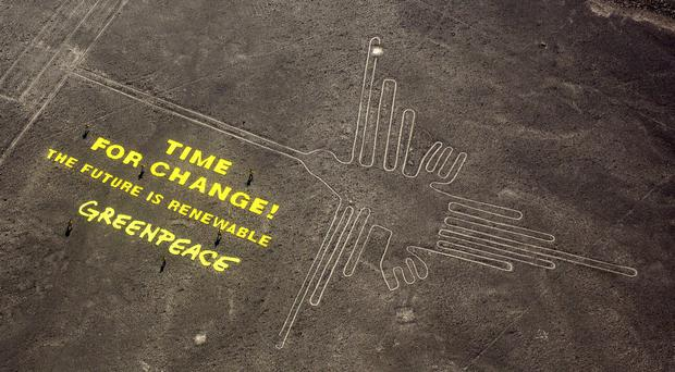 Greenpeace displayed a message next to the hummingbird geoglyph in Nazca, Peru (AP)