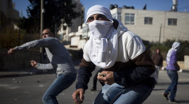 West Bank youths clash with Israeli soldiers after the funeral of Palestinian cabinet member Ziad Abu Ain. (AP)