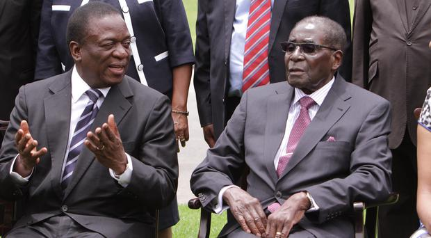Emmerson Mnangagwa, left, chats with Robert Mugabe after the swearing-in ceremony. (AP)