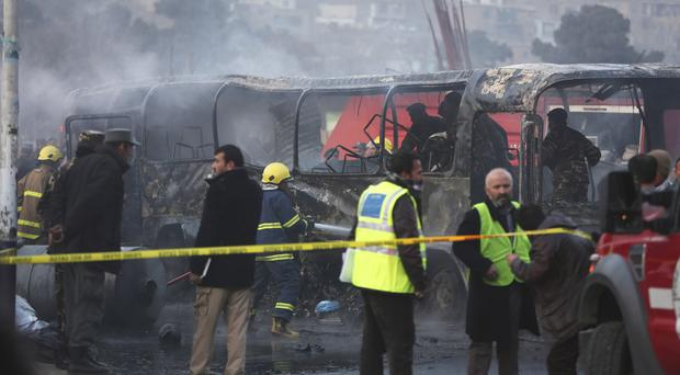 Afghan security guards inspect a damaged bus at the site of a suicide attack in Kabul (AP Photo/Rahmat Gul)