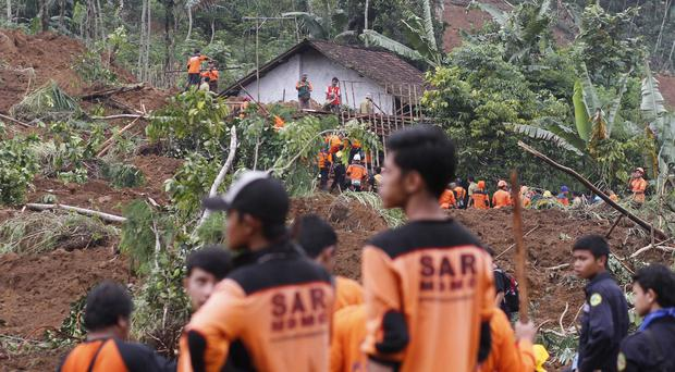 Rescuers search for the victims of a landslide that swept away a village in Indonesia (AP)
