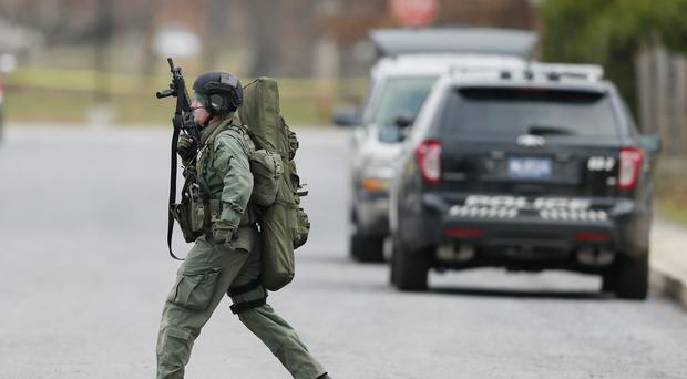 A police officer moves near a home in Souderton, Pennsylvania, where a suspect is believed to have barricaded himself inside after shootings at multiple homes (AP)