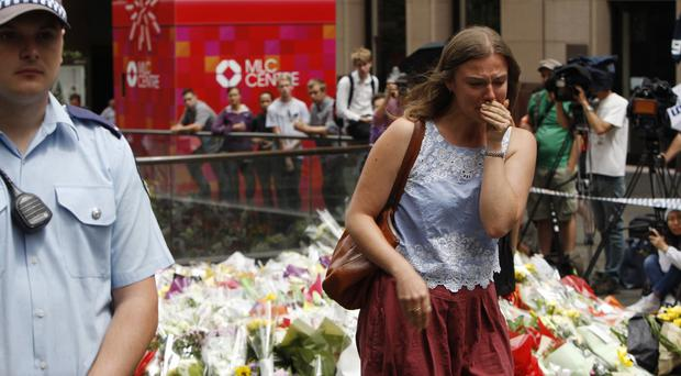 A woman cries after laying a flower at the makeshift memorial in Sydney (AP)