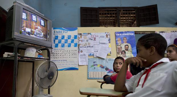 Students watch a speech by President Raul Castro about the country's restoration of relations with the United States at school in Havana (AP)