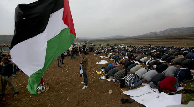 Palestinians protesters pray for Palestinian Cabinet minister Ziad Abu Ain, who collapsed shortly after a protest on December 10 in the village of Turmus Aya near the West Bank city of Ramallah (AP)