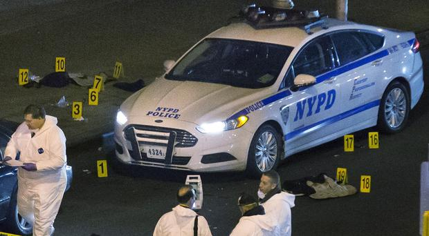 Forensic experts examine the scene where two New York police officers were murdered in their car (AP)
