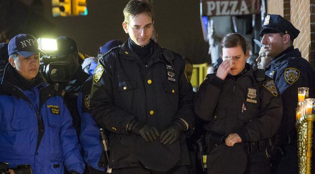 Colleagues grieve near the spot where two New York police officers were murdered in their patrol car (AP)