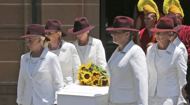 White Lady funeral directors carry the coffin of Tori Johnson during a funeral service in Sydney (AP)