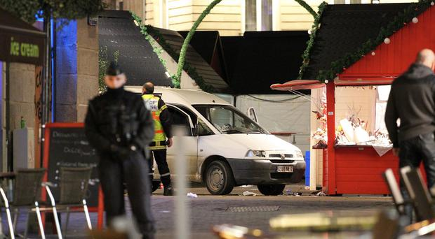 Police officers guard a van which crashed into a Christmas market in Nantes, western France (AP Photo/Laetitia Notarianni)