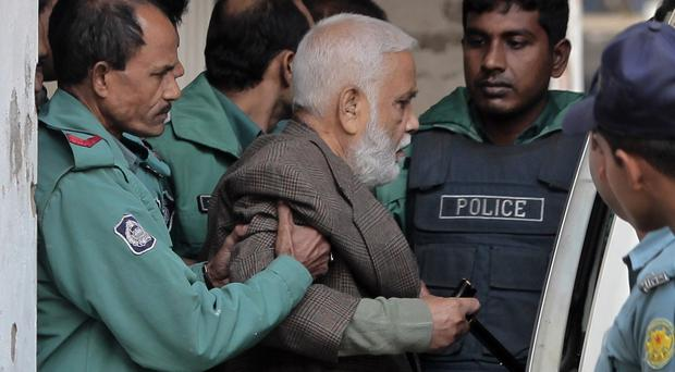 Bangladeshi police escort 73-year-old Syed Mohammed Kaiser into a van after he was sentenced to death in Dhaka. (AP)