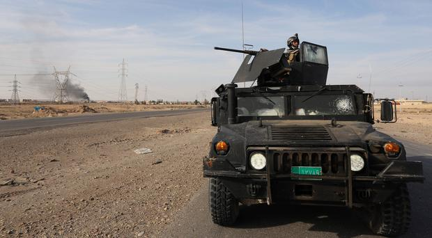 Iraqi security forces on patrol around the town of Beiji. (AP)