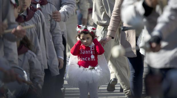 A Palestinian girl dressed in a costume with 'Santa's princess' written on it joins a Christmas Eve celebration at Manger Square in Bethlehem (AP)