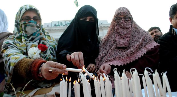 Women light candles to pay tribute to students killed in a Taliban attack, in Peshawar, as tough anti-terror measures are planned (AP)