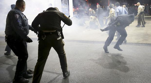 Police try to control a crowd at the petrol station where the teenager was shot (AP/St. Louis Post-Dispatch)