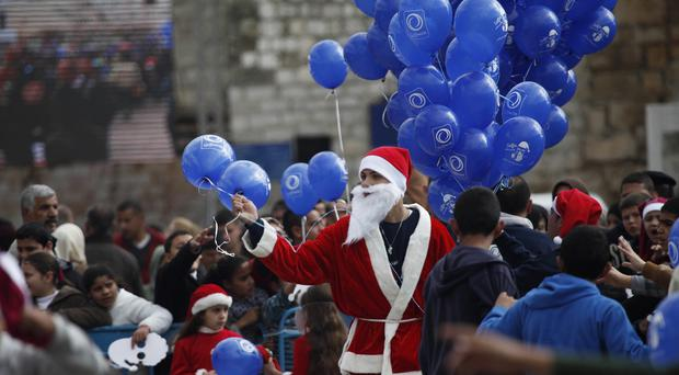 A Palestinian dressed as Santa Claus holds balloons at Manger Square . (AP)