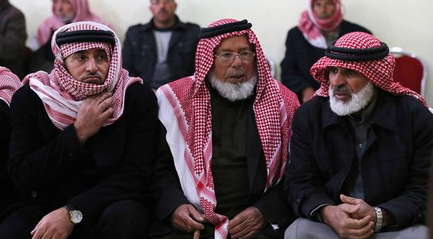 Relatives and friends of Mu'ath Safi al-Kaseasbeh gather in the town of Aey near Al Karak, in southern Jordan (AP)