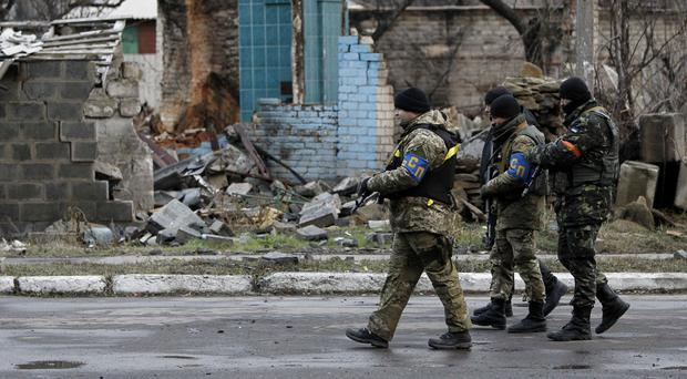 Ukrainian government army soldiers patrol an area in the village of Debaltseve, Donetsk (AP)