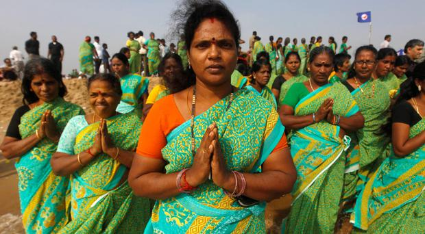 Indian women offer prayers on Marina Beach in the Bay of Bengal for the tsunami victims