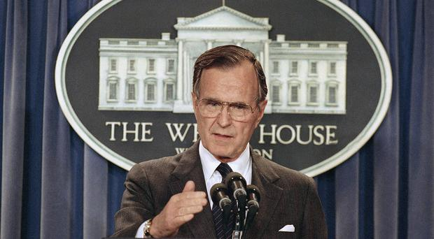 Former US president George HW Bush, pictured briefing reporters at the White House in 1989, is to remain in a Houston hospital (AP)