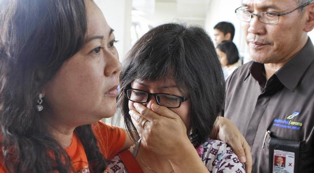 A relative of AirAsia flight QZ8501 passengers weeps as she waits for news at Juanda International Airport (AP)