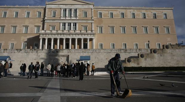 A worker cleans the plaza in front of the Parliament building in Athens (AP)