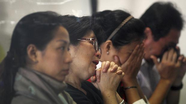 Relatives and next-of-kin of passengers on the AirAsia flight QZ8501 wait for the latest news in Surabaya (AP)