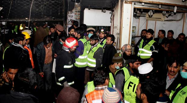 People gather at the entrance of a damaged building after a fire broke out in a Lahore shopping centre (AP)
