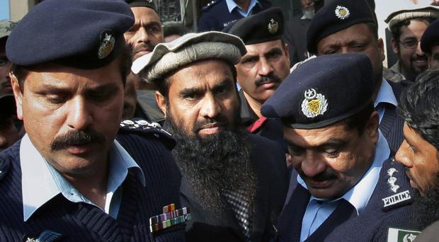 Pakistani police officers escort Zaki-ur-Rahman Lakhvi, centre, the main suspect in the Mumbai terror attacks in 2008, after his court appearance in Islamabad (AP)