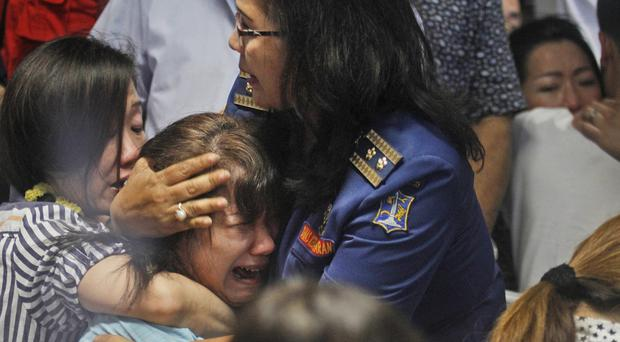 Relatives of passengers of the missing plane react after hearing that bodies had been found (AP)
