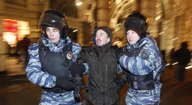 Police detain a protester during an unsanctioned protest in Moscow after Alexei Navalny was found guilty of fraud and given a suspended sentence (AP Photo/Denis Tyrin)