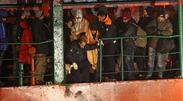 A ship carrying hundreds of migrants arrives at a southern Italian port (AP)
