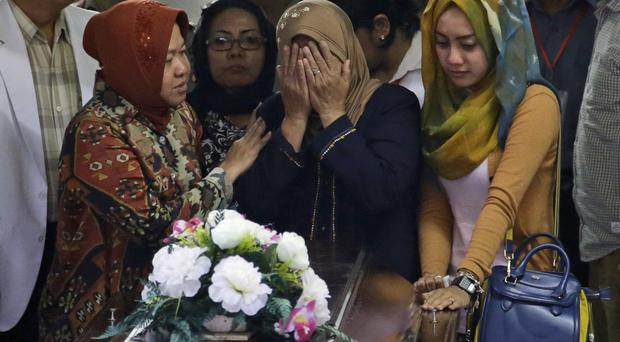 The body of Hayati Lutfiah, one of the victims of AirAsia Flight 8501, is handed over to weeping relatives (AP)