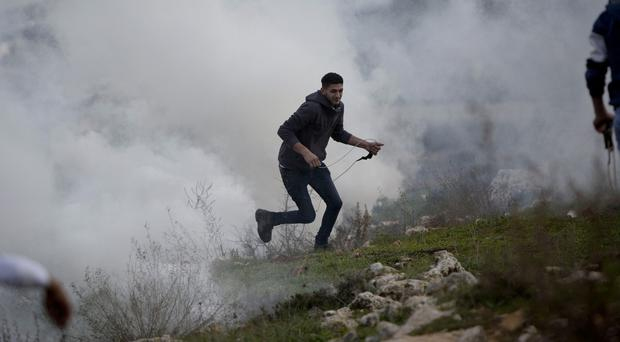 A Palestinian protester runs from tear gas fired by Israeli troops near the West Bank city of Ramallah. (AP)