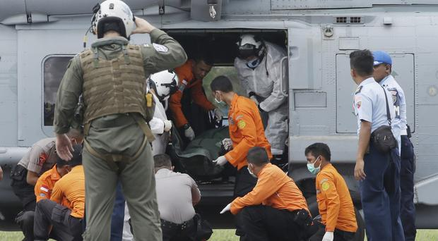 A body is unloaded from a US Navy helicopter on to the USS Sampson (AP)