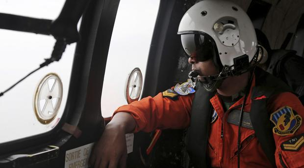 An Indonesian Air Force helicopter crew member scans the sea for the victims and wreckage of the AirAsia plane (AP)