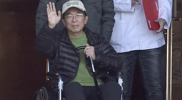 Former Taiwan president Chen Shui-bian waves to supporters as he is wheeled in a chair from prison in Taichung (AP)