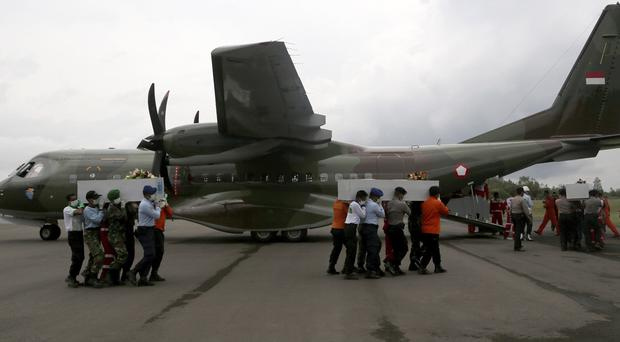 National Search And Rescue Agency officials and Indonesian soldiers carry the coffins of AirAsia victims at the airport in Pangkalan Bun (AP)