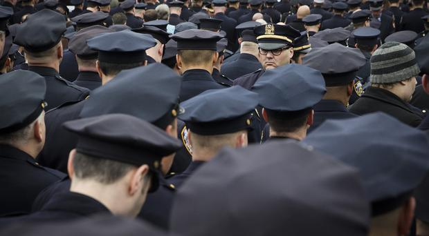 Police officers turn their backs while Mayor Bill de Blasio speaks during the funeral of Wenjian Liu (AP)