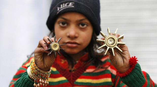 An Indian border girl displays a mortar shell allegedly fired from the Pakistan side of the border at Bainglad village in Samba sector, about 32 miles from Jammu, India (AP)