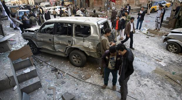 Shiite Houthi men stand near a car damaged by a bomb explosion in Sanaa on December 23 (AP)