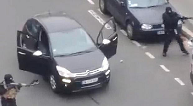 The two gunmen brandishing assault rifles on a Paris street after their attack on the magazine offices