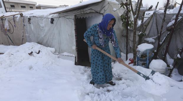 A Syrian woman removes snow from around her tent at a refugee camp in al-Majdal village, Bekaa valley, east Lebanon (AP)