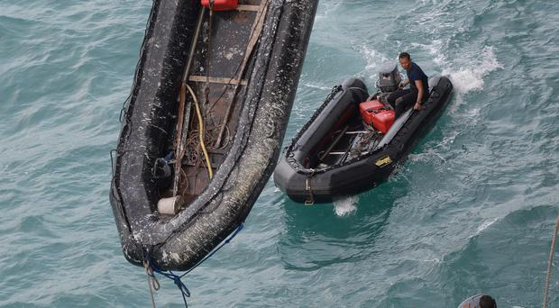 Indonesian navy divers conduct operations to lift the tail of AirAsia Flight 8501 on the Java Sea